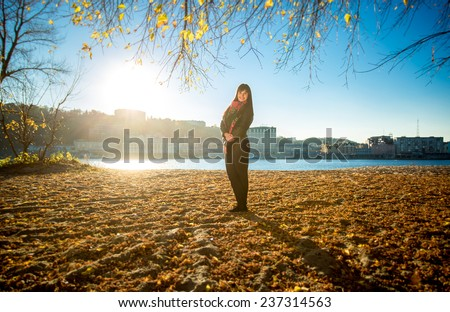 Happy woman posing on sandy river beach at sunny autumn day - stock photo