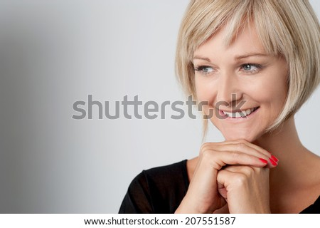 Happy woman posing with hands on chin - stock photo