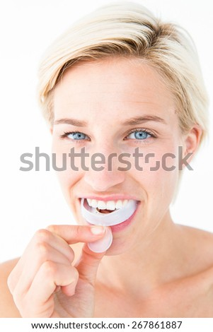 Happy woman putting her gum shield on white background - stock photo