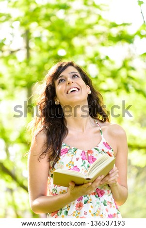 Happy woman reading and holding an open story book in fresh green park on spring or summer day. Caucasian woman smiling and enjoying outdoors. - stock photo
