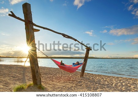 Happy woman relaxes, lying in a hammock in sunny spring day. enjoy sunset at hammock                                         - stock photo