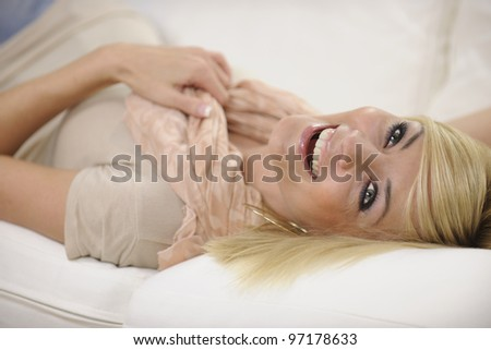 Happy woman relaxing at home laughing on sofa - stock photo