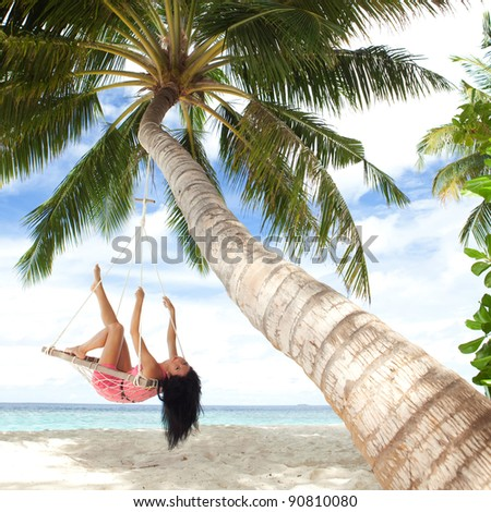 Happy woman relaxing in hammock on a tropical beach - stock photo