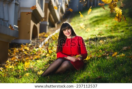 Happy woman relaxing on grass at park with leaves flying around - stock photo