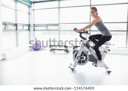 Happy woman riding an exercise bike in gym - stock photo