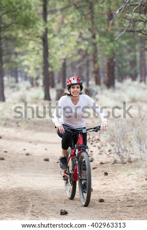 Happy woman riding mountain bike on wilderness trail - stock photo