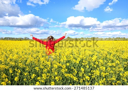 Happy woman running through a colza field. - stock photo