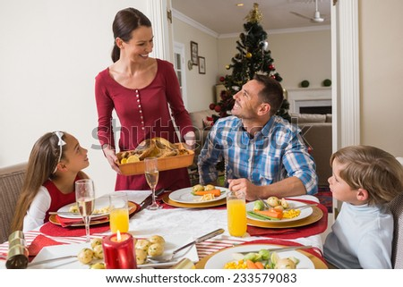Happy woman serving roast turkey to her family at home in the living room - stock photo