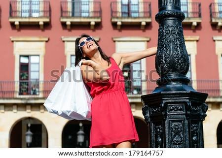 Happy woman shopping in Spain. Joyful girl in red dress having fun and dancing on european travel. - stock photo