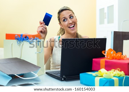 Happy woman shopping online at computer holding credit card and the table full shopping bags - stock photo