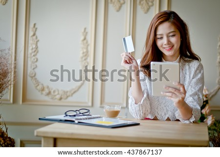 Happy woman shopping online, holding credit card, using tablet computer, electronic purchase. - stock photo