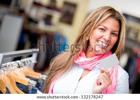 Happy woman shopping with a credit card in a retail store - stock photo