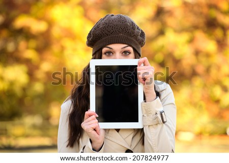 Happy woman showing digital tablet blank screen in autumn season. Brunette caucasian female covering her face with touchpad frame for copy space message or information. - stock photo