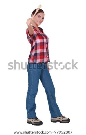 Happy woman showing paintbrush - stock photo