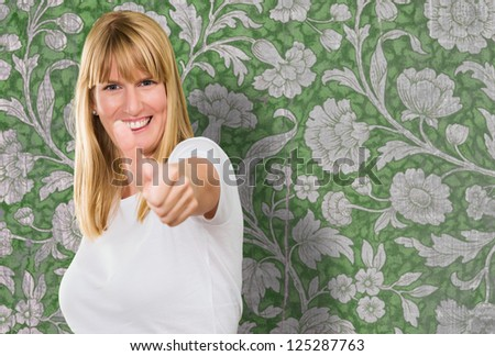 Happy Woman Showing Thumb Up against a floral vintage background - stock photo