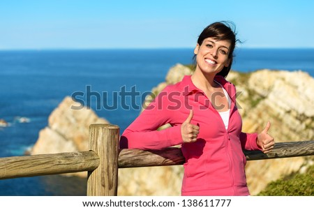 Happy woman sitting and relaxing on sea and coast landscape background. Pensive girl enjoying peace and silence on nature summer vacation. Asturias, Spain. - stock photo