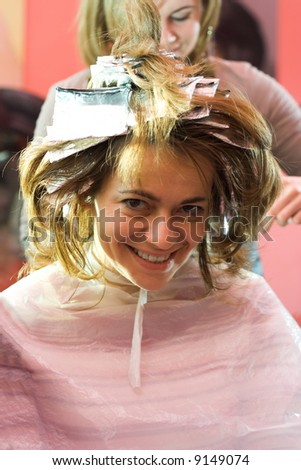 Happy woman sitting at the hair stylist, her hair is being bleached - stock photo