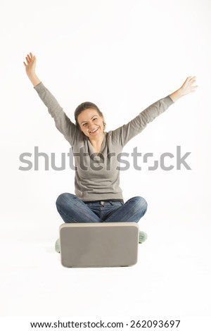 Happy woman sitting cross legged on floor with a laptop and arms raised up, on white background. Work from home. On-line study. - stock photo