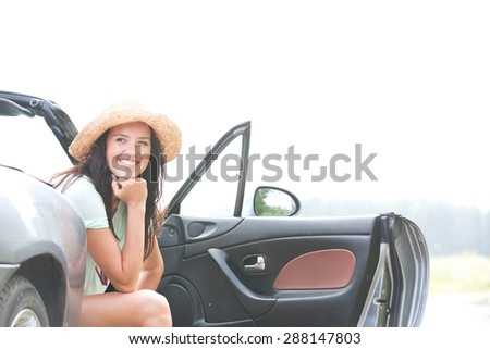 Happy woman sitting in convertible against clear sky - stock photo