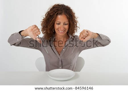 Happy woman sitting in front of an empty dish. Diet concept. You can place the food you prefer in the plate. - stock photo