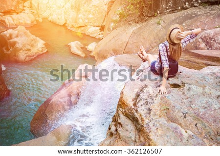 Happy woman sitting on the rock edge near waterfall enjoying stunning view, filtered with sun flares - stock photo