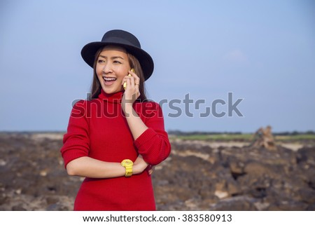 Happy woman smiling and walking in the nature using a smartphone  - stock photo