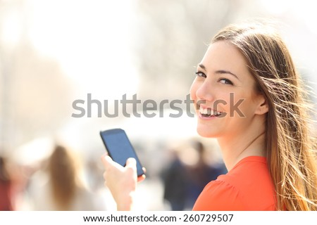 Happy woman smiling and walking in the street using a smartphone and looking at camera  - stock photo