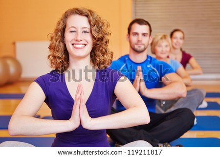 Happy woman smiling in yoga class in a fitness center - stock photo