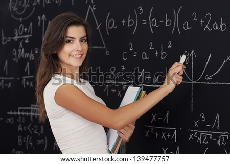 Happy woman solving mathematical problems - stock photo