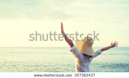 Happy woman standing arms outstretched back and enjoy life on the beach at Sea - stock photo