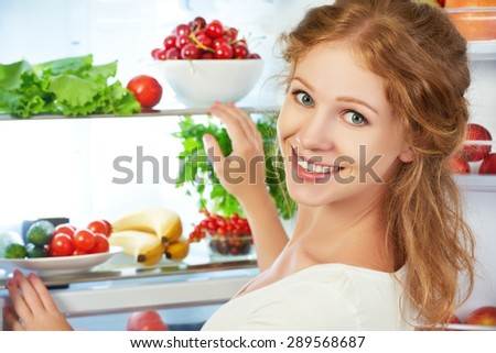 Happy woman standing at the open refrigerator with fruits, vegetables and healthy food - stock photo