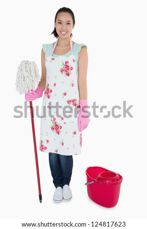 Happy woman standing with mop and bucket - stock photo
