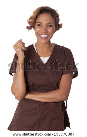 Happy woman stands smiling in scrubs, isolated on white background. - stock photo