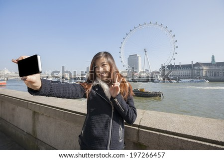 Happy woman taking self portrait through cell phone ; England; UK - stock photo