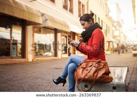 Happy woman texting with her mobile and sitting on a bench in the street - stock photo
