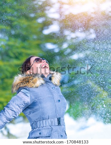 Happy woman throwing snow in wintertime park, enjoying nature, looking up, happy and active winter holidays, fun and joy concept - stock photo