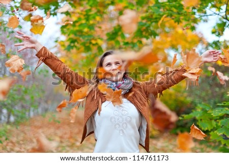 Happy woman throws autumn leaves in the park - stock photo