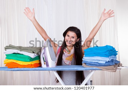 Happy woman throws her arms in the air because she has finished and folded all of the ironing - stock photo