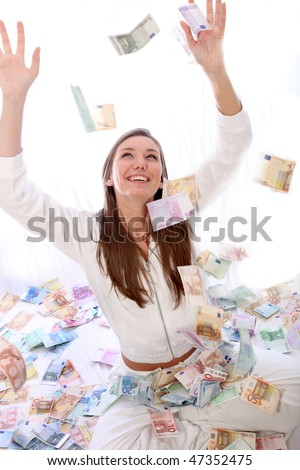 Happy woman throws up many bills - stock photo