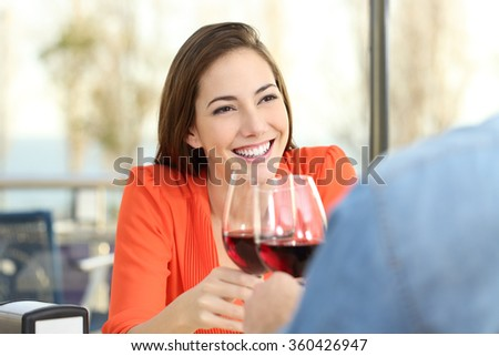 Happy woman toasting with red wine with her partner or friend during a date in a coffee shop interior with a window in the background - stock photo