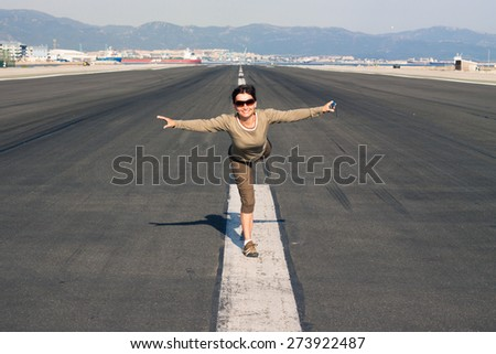 Happy woman tourist imitating airplane at the airport runway. - stock photo