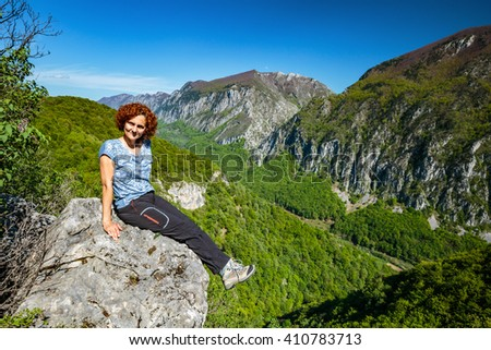 Happy woman tourist on the top of a mountain - stock photo