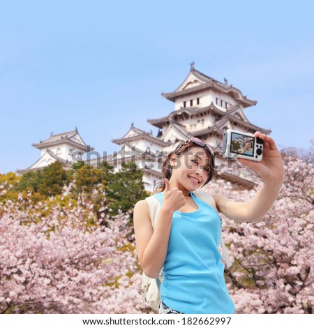 Happy woman traveler take photos by camera with  cherry blossoms tree and castle on vacation in japan while spring - stock photo