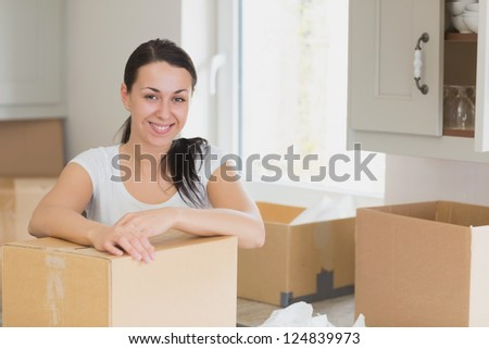 Happy woman unpacking in kitchen - stock photo