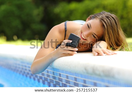 Happy woman using a smart phone in a poolside of her garden pool in summer - stock photo