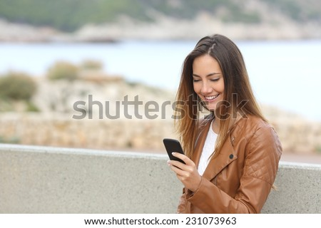 Happy woman using a smart phone on the beach with copy space and the sea in the background - stock photo