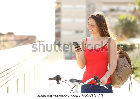 Happy woman using a smart phone walking with a bicycle in an urban park - stock photo