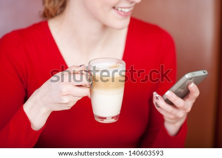 Happy woman using cell phone while holding cafe latte cup in coffee shop - stock photo