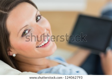 Happy woman using her laptop in the living room - stock photo