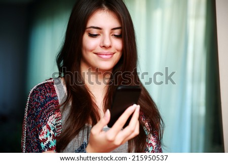 Happy woman using smartphone at home - stock photo
